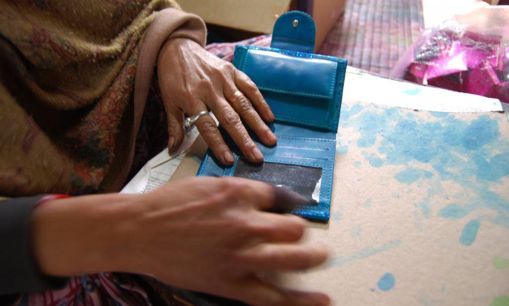 Assembling a leather wallet at Shanti Handicrafts