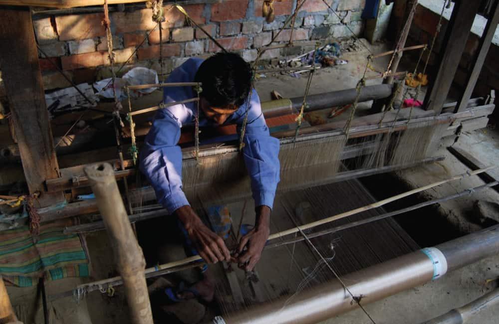 Weaving-man-adjusting-loom